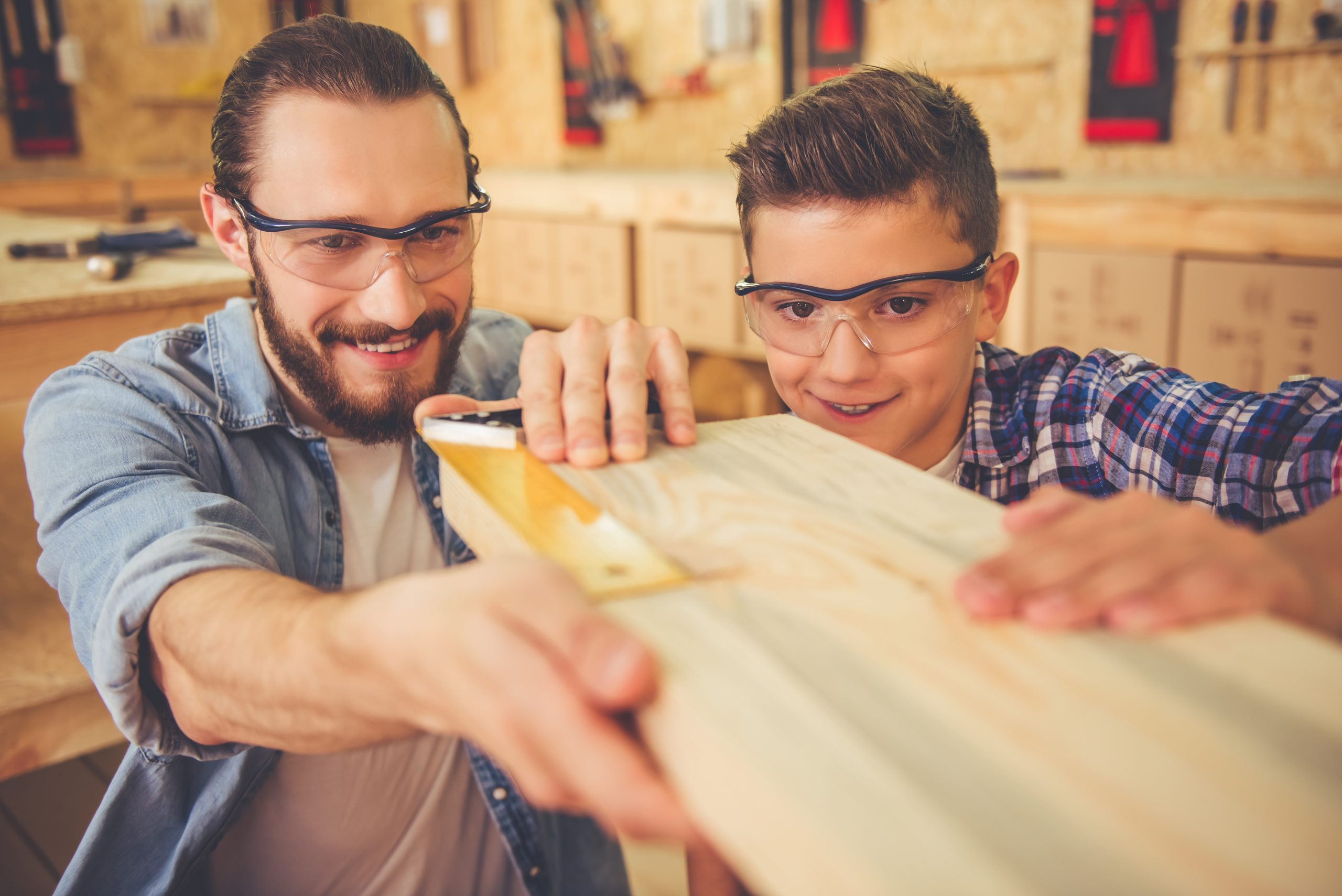 Handsome teenage carpenter and his father in protective glasses are measuring wood and smiling while working in the workshop