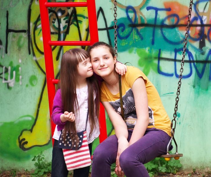 Portrait of beautiful young girls together on playground.